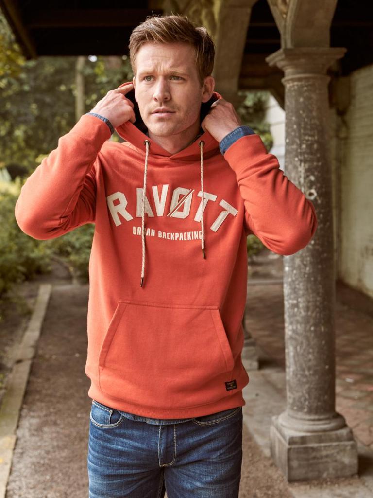 Sweater met kap (49,95 euro) in een warm oranje dat prima matcht met indigoblauw, uit de Ravøtt-collectie van E5.