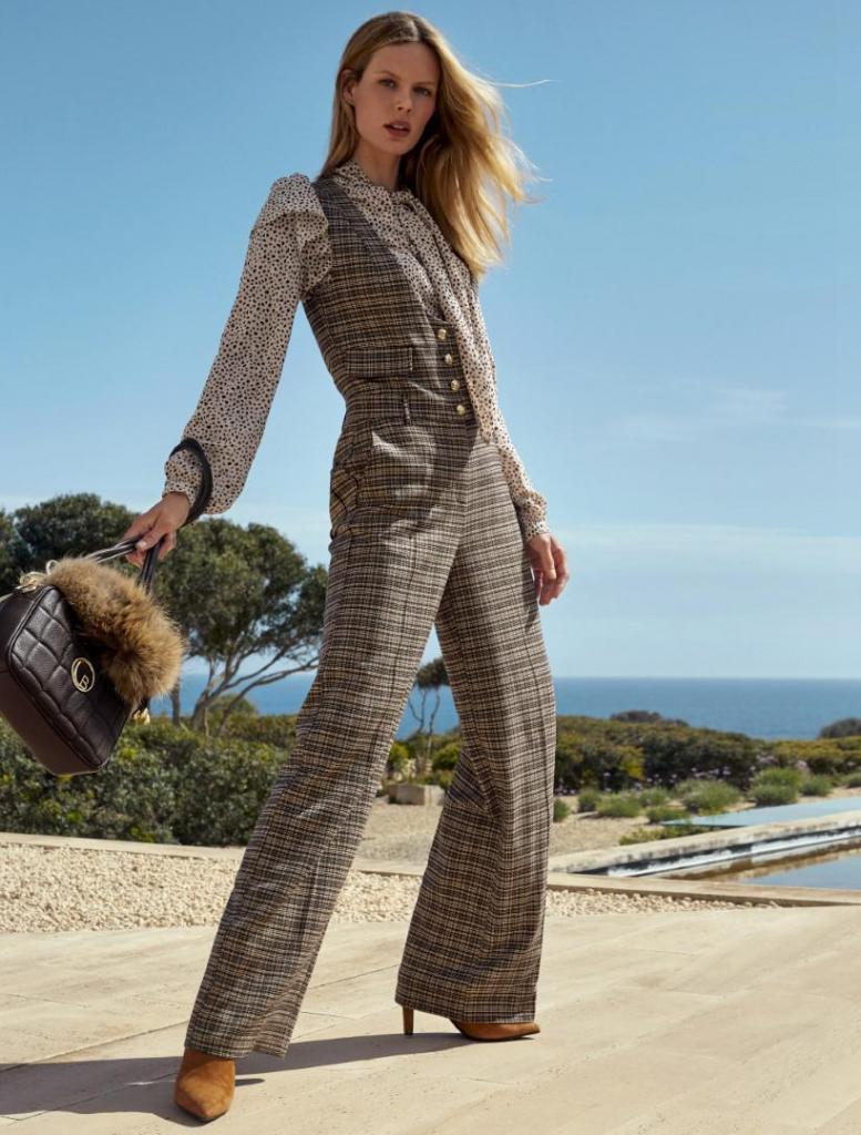 Mix van stoer en vrouwelijk: geruite jumpsuit (220 euro), romantische bloes met strik (175 euro), cognackleurige laarsjes met hoge hak (285 euro) en handtas (165 euro), van Caroline Biss.