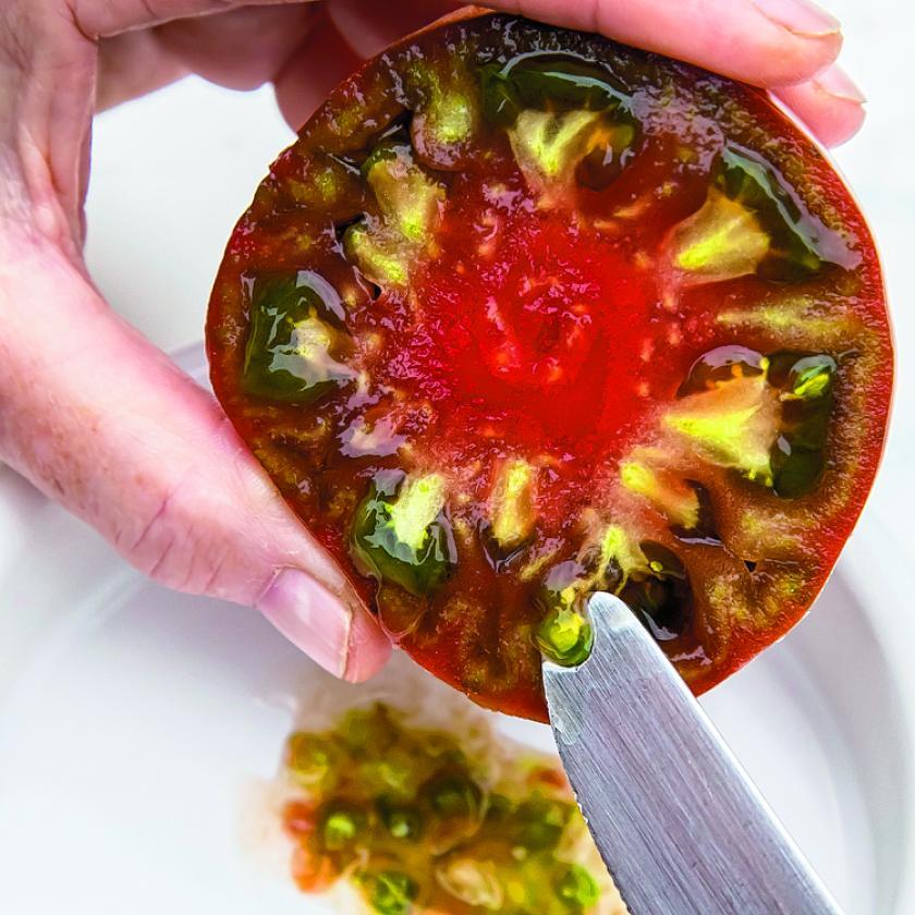 Faire ses propres graines: la tomate est coupée en deux pour en extraire le jus et les graines avant de les faire macérer dans un pot